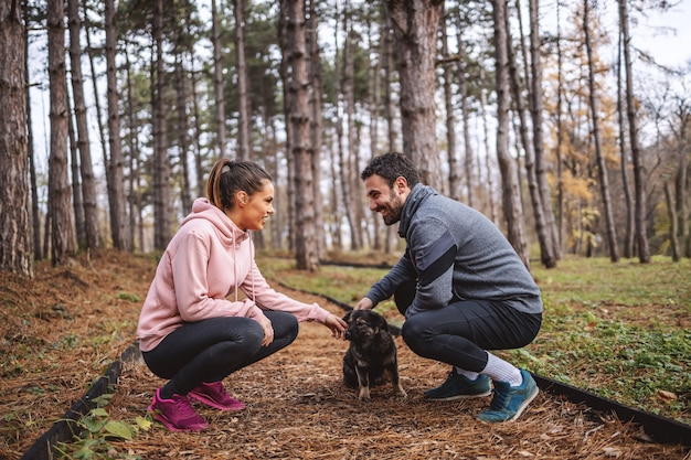 Happy young couple in sportswear crouching on trail in woods, looking at each other and petting stray dog. break after running.