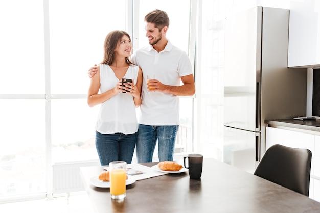 행복 한 젊은 커플 서 부엌에서 아침 식사와 함께 테이블 앞에서 포옹