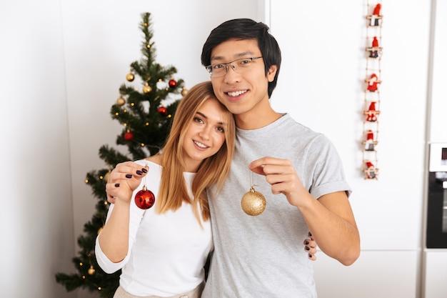 Счастливая молодая пара, стоя у елки дома, празднует