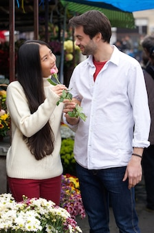 Happy young couple standing by flower shop