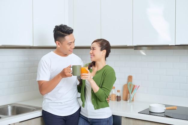 그들의 집에있는 부엌에 서있는 행복 한 젊은 커플.