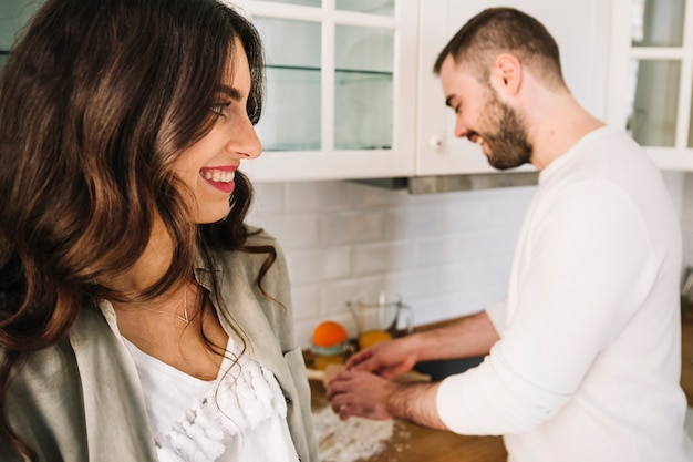 Happy young couple standing on kitchen