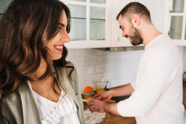 Giovani coppie felici che stanno sulla cucina