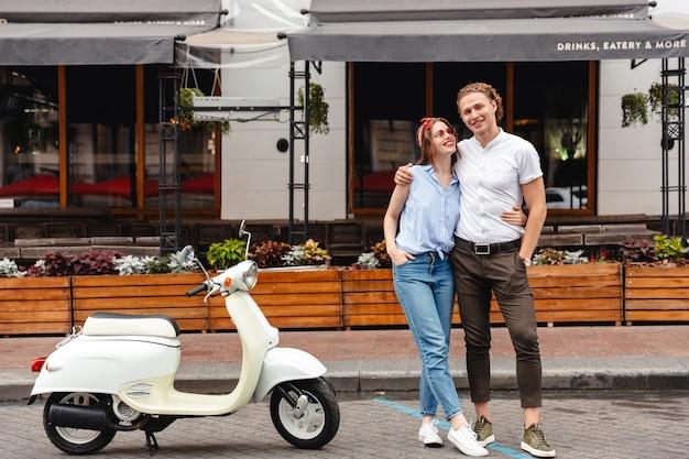 Счастливая молодая пара, стоя вместе с мотоциклом на улице города