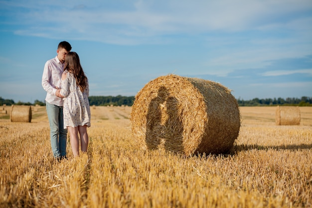 Happy young couple on straw, romantic people , beautiful landscape, summer season