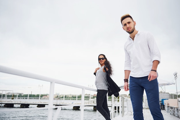 Happy young couple in stylish branded clothes, standing on the pier in the water.