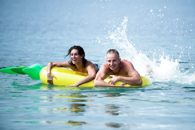 Happy young couple swimming and laughing on air mattress couple vacation concept man and woman on honeymoon swim on pineapple shaped mattress in sea summer accessories for rest