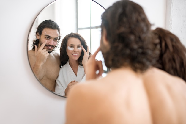 朝、バスルームの鏡の前に立って目の下の世話をしている幸せな若いカップル
