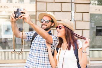 Happy young couple taking selfie on camera in city