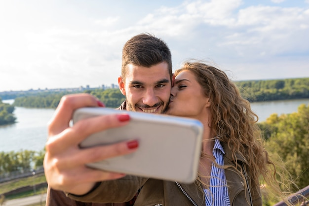 Happy young couple taking selfie photos near the river