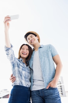 Happy young couple taking a selfie on smartphone outdoors