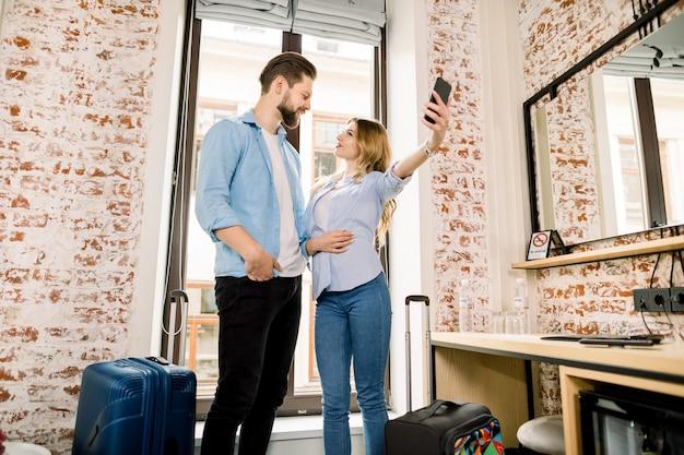 Счастливые молодые пары принимая selfie с мобильным телефоном пока стоящ над предпосылкой окна на гостиничном номере с чемоданами