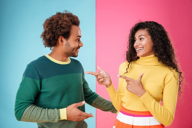 Happy young couple talking and pointing on each other over colorful background