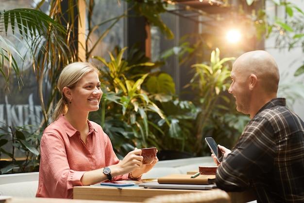 幸せな若いカップルがお互いに話し、カフェでデート中にコーヒーを飲む