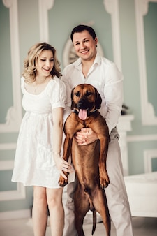 Happy young couple and their favorite dog standing in the living room