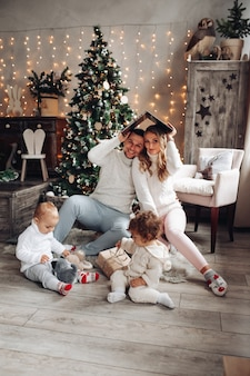Happy young couple and their kids near christmas tree