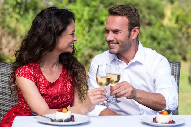 Happy young couple toasting wine in lawn