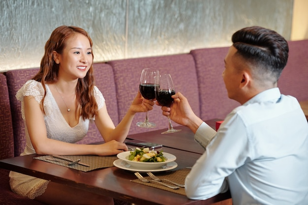 Happy young couple toasting with wine glasses when enjoying romantic date in nice restaurant