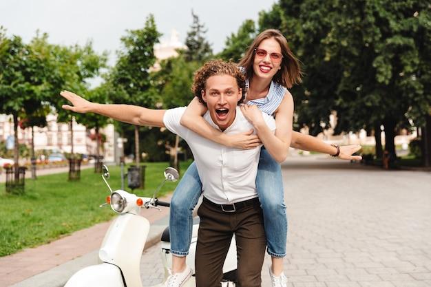 Счастливая молодая пара вместе на мотоцикле на городской улице, смеясь, весело