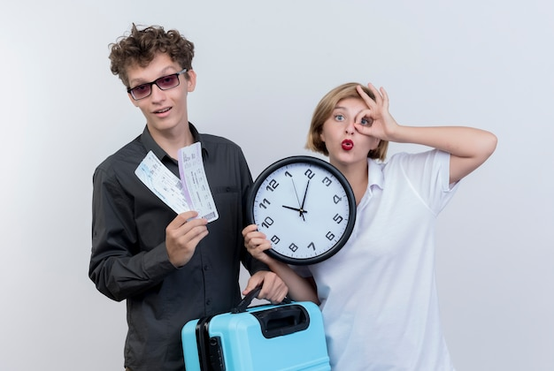 Felice giovane coppia di turisti uomo che tiene in possesso di biglietti aerei e valigia con la donna che tiene l'orologio da parete facendo ok cantare in piedi sopra il muro bianco