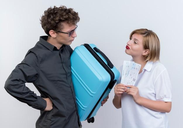 Felice giovane coppia di turisti uomo che tiene la valigia guardando la sua fiduciosa fidanzata con biglietti aerei nelle mani sopra bianco