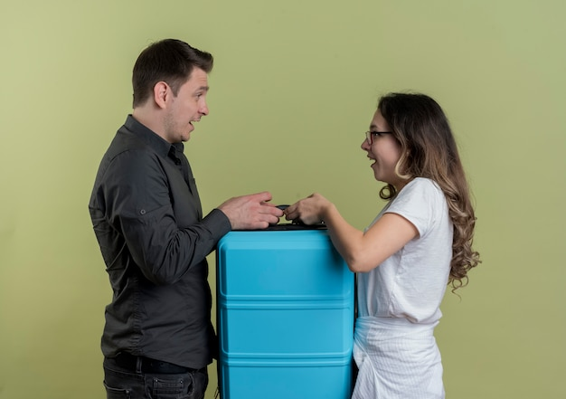 Felice giovane coppia di turisti uomo e donna che tiene la valigia guardando l'altro sorridente sopra la parete chiara