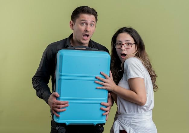 Felice giovane coppia di turisti uomo e donna che tiene la valigia che sembra sorpreso in piedi sopra la parete leggera