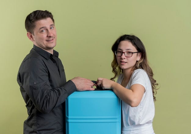 Felice giovane coppia di turisti uomo e donna che tiene la valigia sorridente sopra la parete chiara