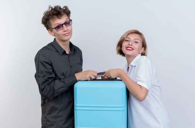 Felice giovane coppia di turisti uomo e donna che tiene la valigia sorridente sopra il muro bianco