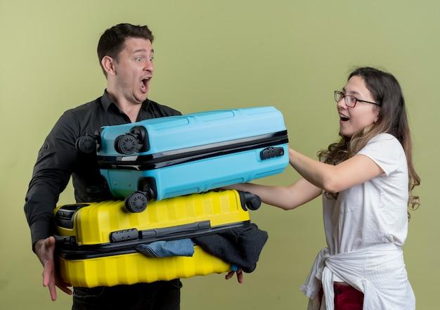 Felice giovane coppia di turisti uomo e donna che tengono le valigie in piedi sopra la parete chiara