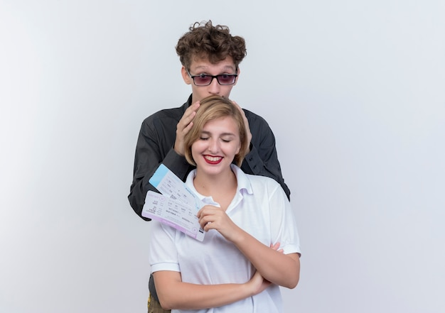 Felice giovane coppia di turisti uomo e donna con biglietti aerei divertendosi insieme in piedi sopra il muro bianco