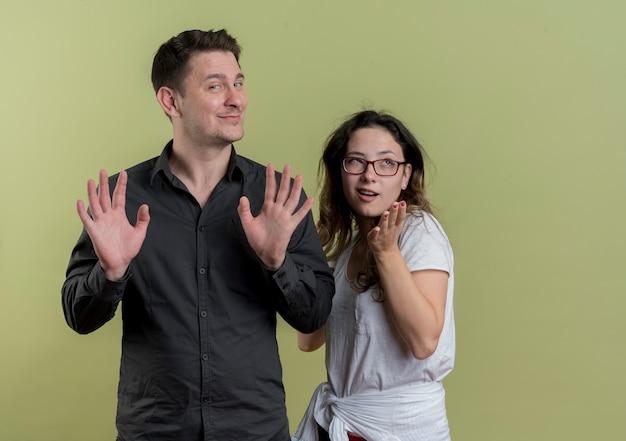 Felice giovane coppia di turisti uomo e donna con le braccia fuori cercando confuso in piedi sopra la parete chiara