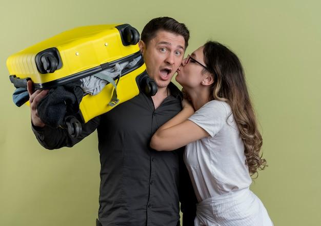 Felice giovane coppia di turisti donna che bacia il suo fidanzato mentre tiene la valigia piena di vestiti alla ricerca confusa sulla parete chiara