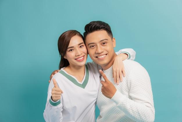 幸せな若いカップル2つの親指アップサイン