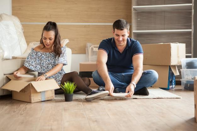 Счастливая молодая пара, распаковывая коробки в своей новой квартире. пара, сидя на полу.