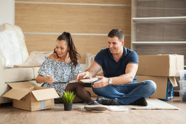Happy young couple unpacking boxes in their new flat.couple sitting on the floor.