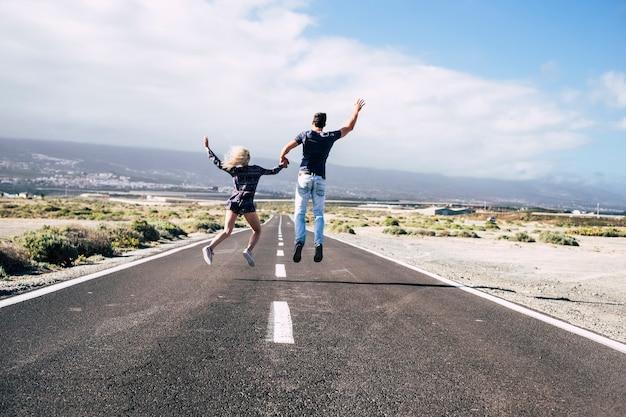 幸せな若いカップルは愛と友情と一緒に歩きます。永遠の人生とポジティブな雰囲気のコンセプトで、lognwayroadとjumpforhappy。家族結婚スタイル