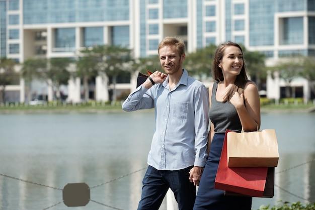 セールで購入した後、買い物袋を持って街の池を歩いている幸せな若いカップル