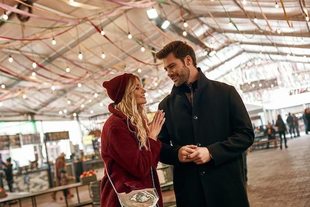 거리 음식 시장을 걷고 있는 행복한 젊은 부부는 사진에서 사람들을 흐리게 합니다.