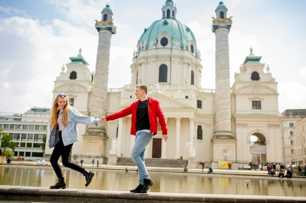Happy young couple walking by st. peter's catholic church in vienna, austria