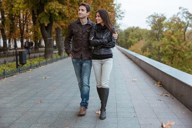 秋の公園を歩く幸せな若いカップル