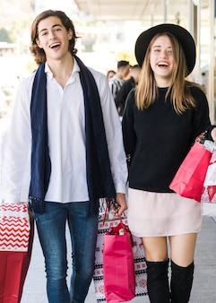 Счастливая молодая пара, ходить на улице с сумок