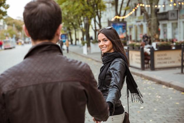 旧市街で屋外を歩く幸せな若いカップル