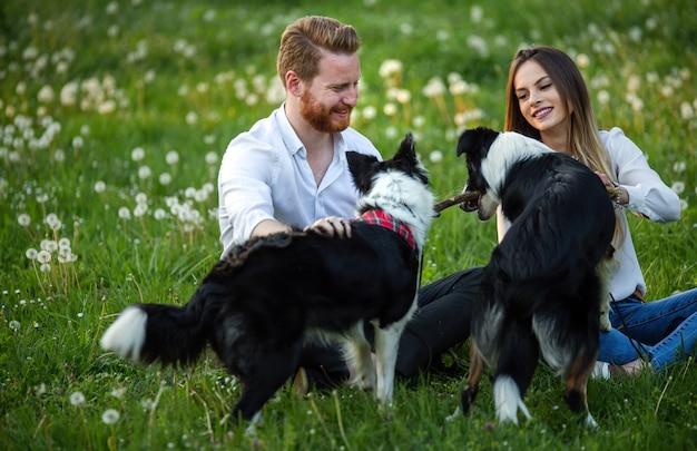 Счастливая молодая пара гуляет, играя с собаками в парке на открытом воздухе