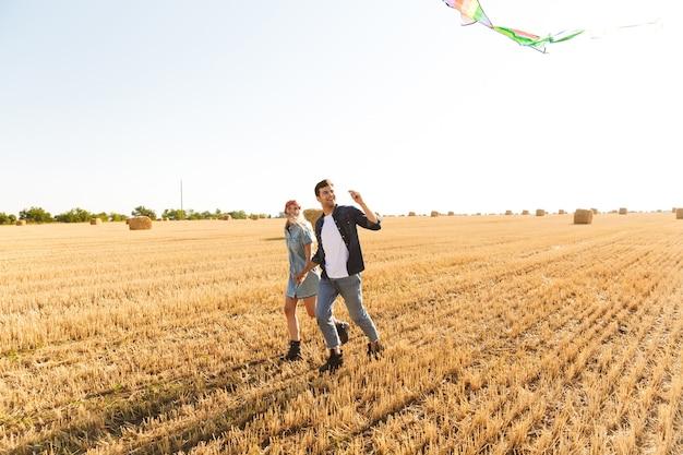 麦畑で一緒に歩いて幸せな若いカップル