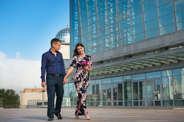 Happy young couple walking together holding hands near modern building.