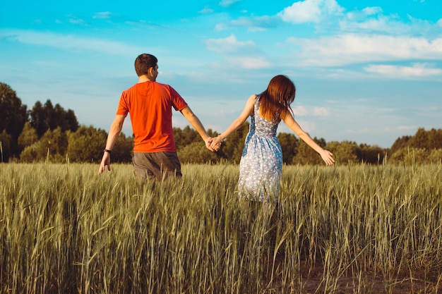 麦畑を一緒に歩いて幸せな若いカップル。背面図。