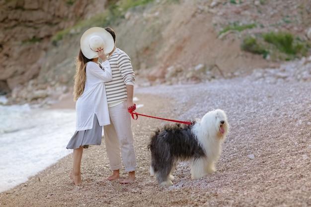 Счастливая молодая пара гуляет с большой собакой на пляже летом