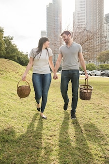 Happy young couple walking with wicker basket in the park