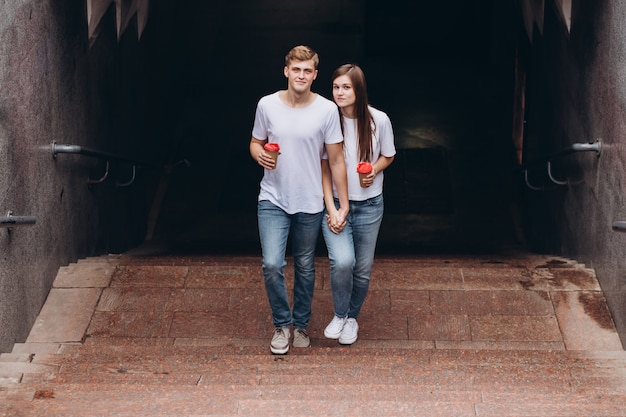 Happy young couple walks the streets of the city and drinks coffee from a cardboard cup.